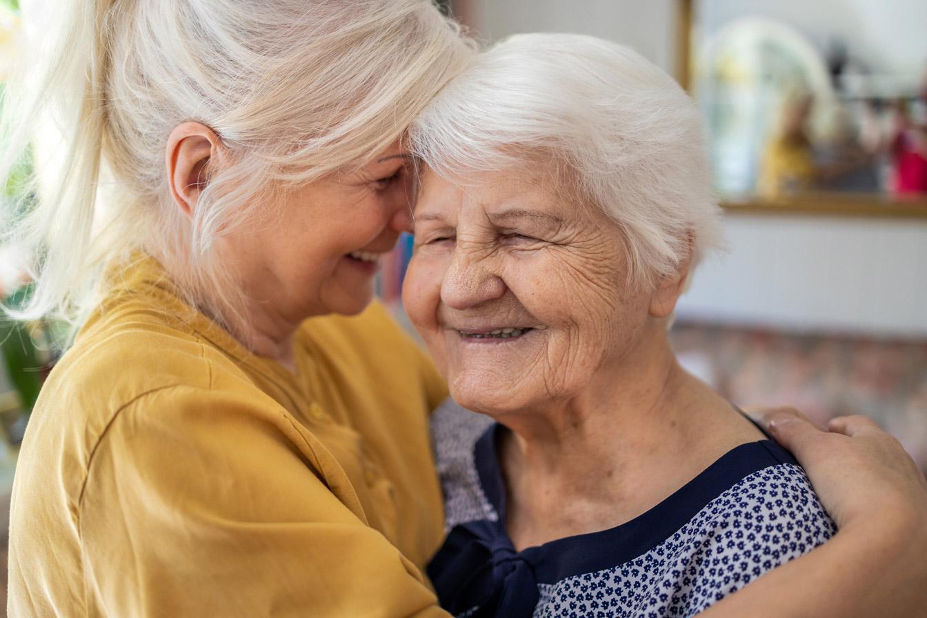 Older adult embracing elderly loved one