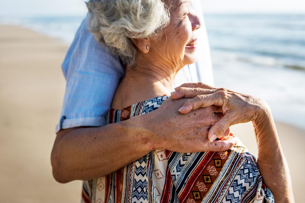 Adult child with hand on elder parent's shoulder